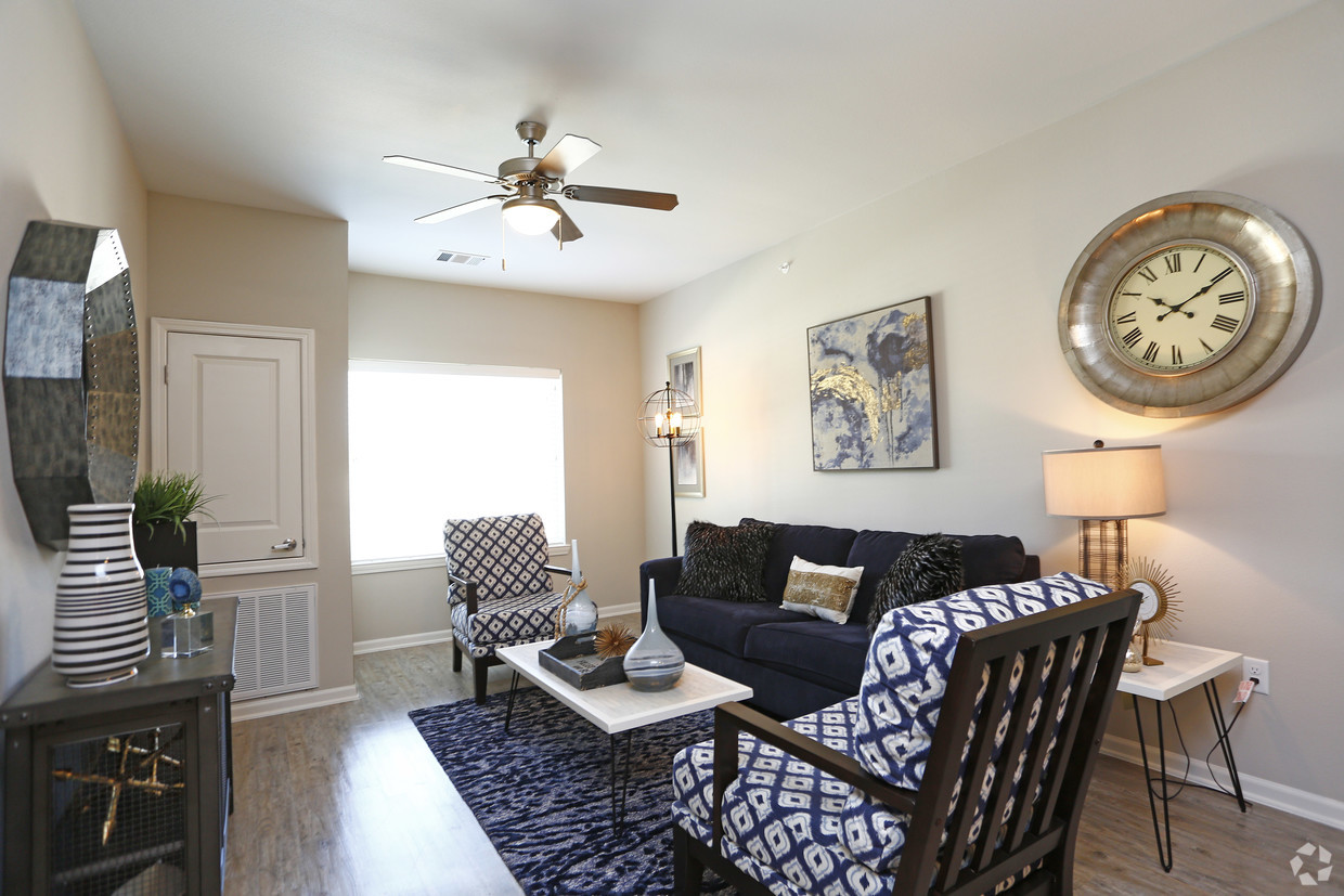 Living room at Goodnight Commons with a sofa, two accent chairs, and a blue area rug