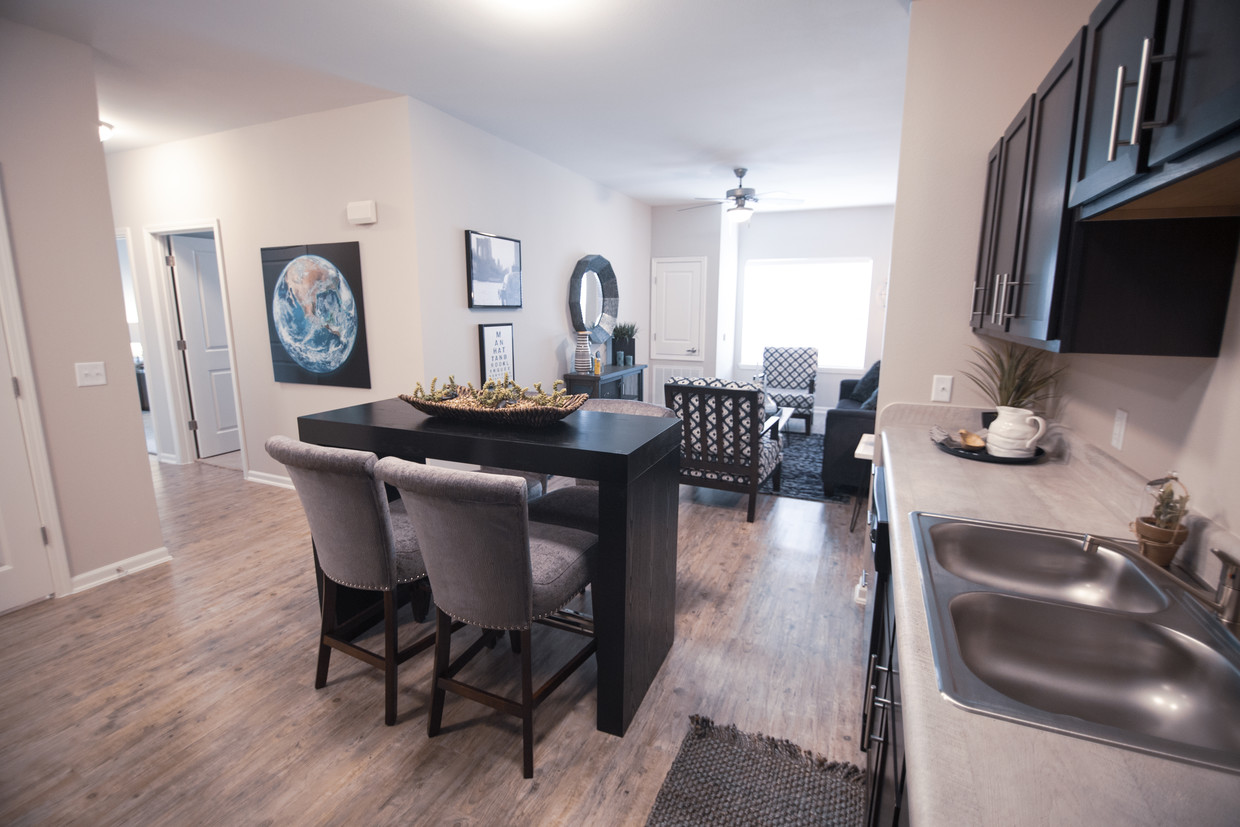 Kitchen area at Goodnight Commons Apartments in Southeast Austin with an island and four grey chairs