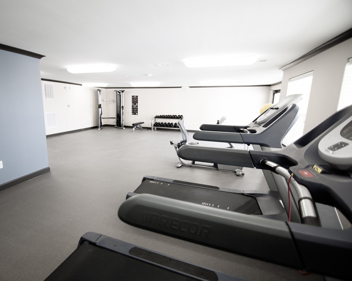 Fitness Center at Goodnight Commons with three treadmills, free weights, and a cable machine