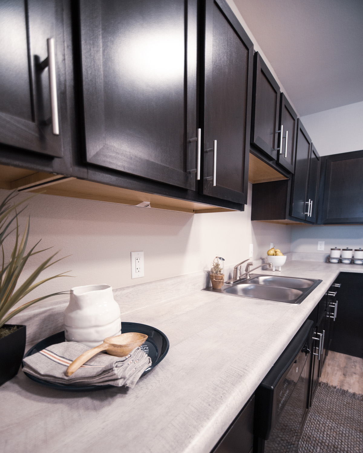 Kitchen area at Goodnight Commons with dark brown cabinets, hard-surface countertops, and a dual sided sink.