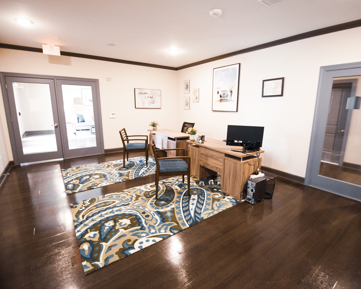 Leasing office at our Southeast Austin apartments with two wood desks and two patterned area rugs on top of hardwood floors