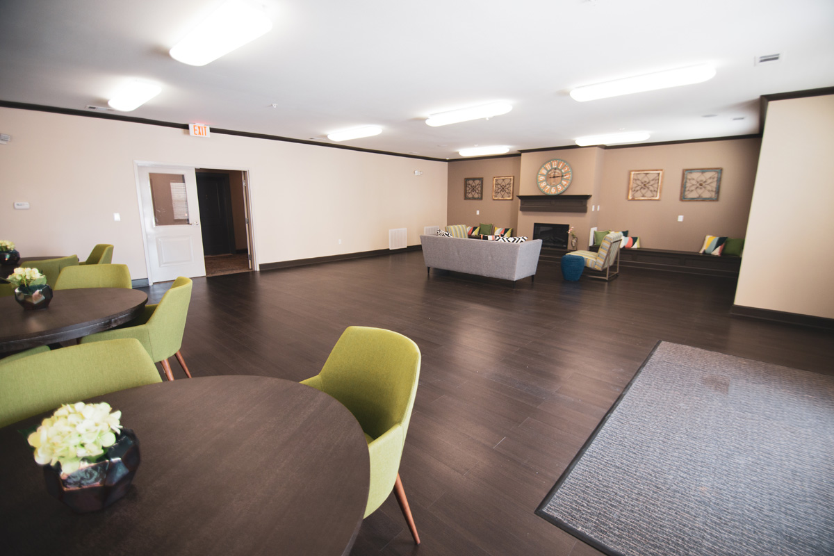 Goodnight Commons clubhouse with hardwood flooring, a grey couch, and two striped lounge chairs surrounding a fireplace