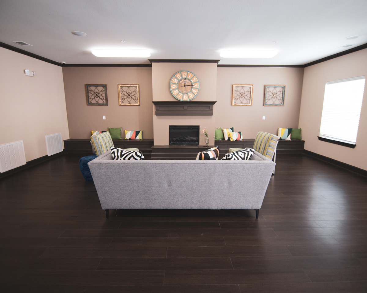 Clubhouse room at Goodnight Commons with a grey couch and two striped green chairs in front of a fireplace