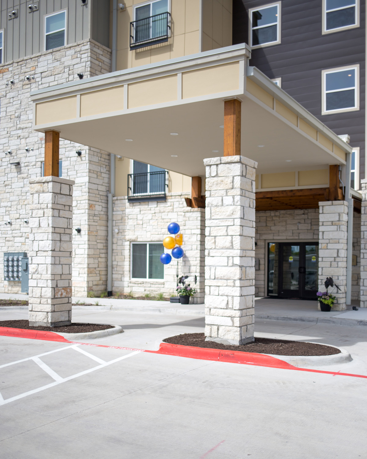 Exterior entrance of Goodnight Commons with a car port and pillars surrounded by stone